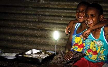 Shenina's children eat their evening meal by the light of the family's solar lamp.